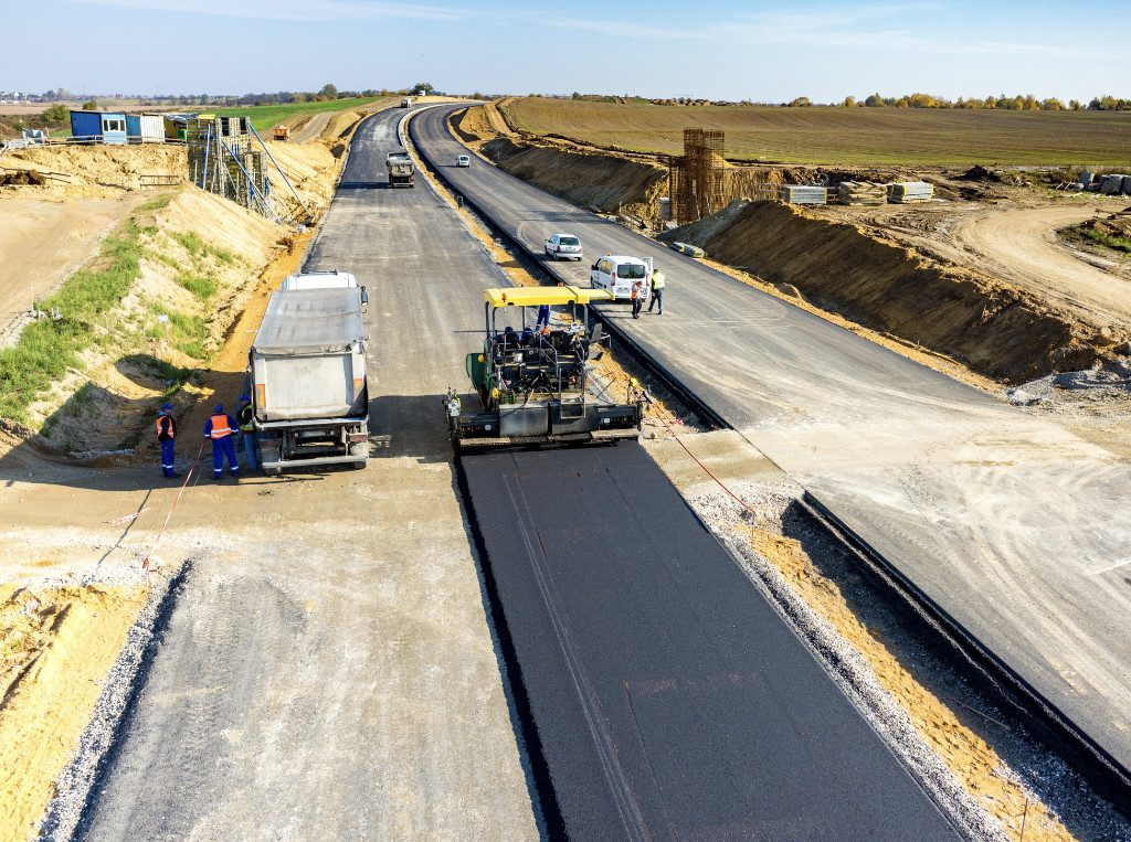 paver machine laying tar down on roads
