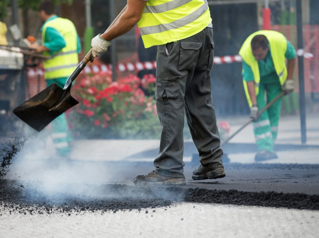 removing excess tar from edges of road