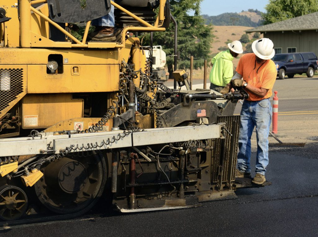 worker running paver machine
