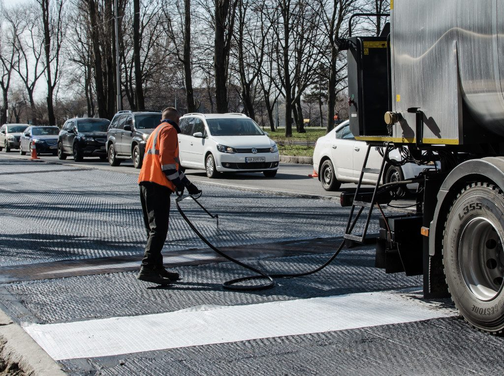 worker sealcoating city streets