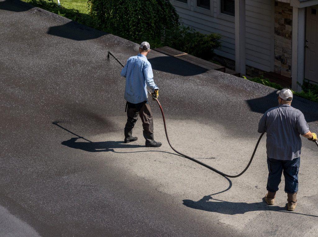 workers applying asphalt sealcoat