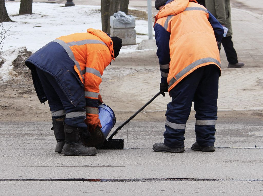 workers filling road cracks with tar